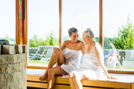 sauna: Senior and young woman in sauna sweating in heat Stock Photo