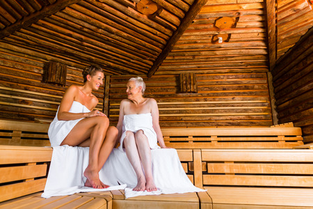 Senior and young woman in sauna sweating in heat Stock Photo