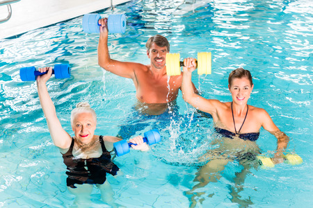 water aerobics: Group of people, mature man, young and senior women, at water gymnastics or aquarobics Stock Photo