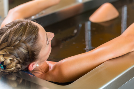 woman in bath: Senior woman enjoying mud bath alternative therapy