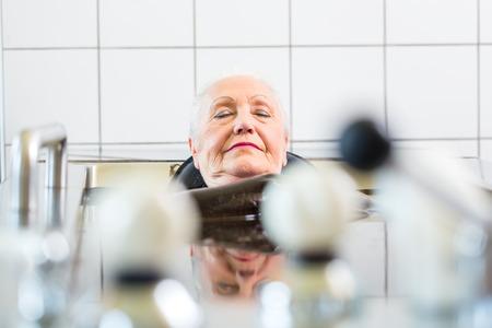 Senior woman enjoying mud bath alternative therapy photo