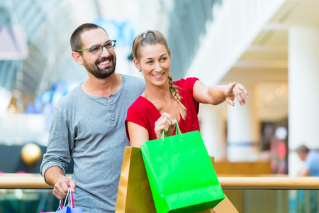 Couple, man and woman, in modern shopping mall with bag photo