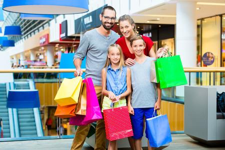 Gezin van vier in winkelcomplex met zakken Stockfoto