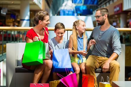 centro comercial: Familia con hijos de compras en el centro comercial que tiene una rotura