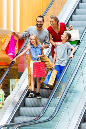 niños de compras: Familia en la alameda de compras en las escaleras mecánicas con bolsas
