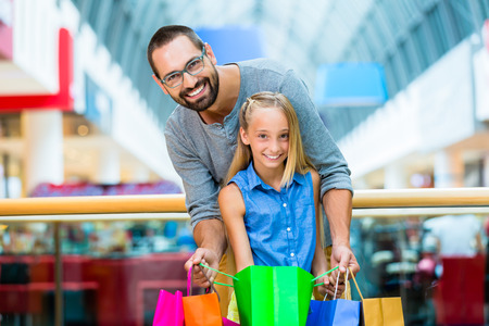 Dad with daughter shopping in mall