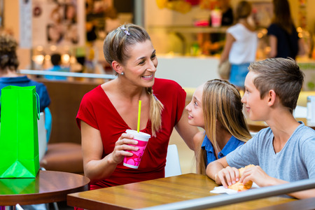 Family eating and drinking in cafe at shopping mall photo