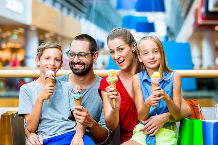 Family eating ice cream in shopping mall with bags Foto de archivo