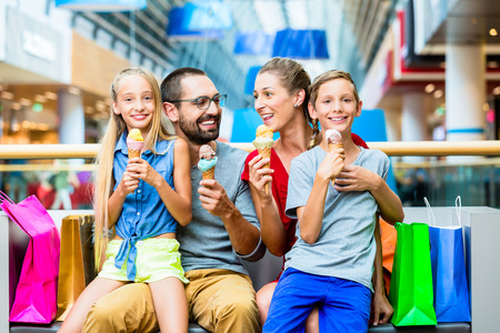 ice cream woman: Family eating ice cream in shopping mall with bags Stock Photo