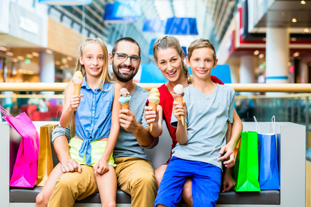 eating ice cream: Family eating ice cream in shopping mall with bags Stock Photo