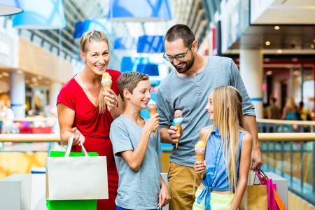 niños de compras: Familia que come el helado en centro comercial con bolsas