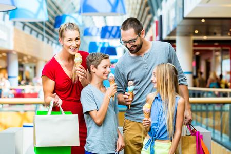 woman with ice cream: Family eating ice cream in shopping mall with bags Stock Photo