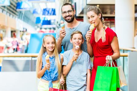 comiendo helado: Familia que come el helado en centro comercial con bolsas