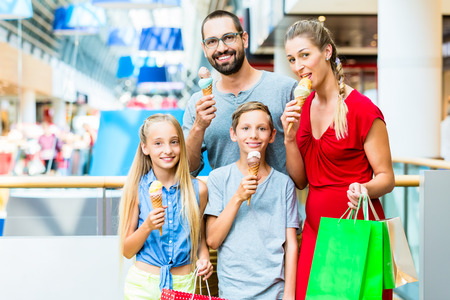 Family eating ice cream in shopping mall with bags Stock Photo - 37893843