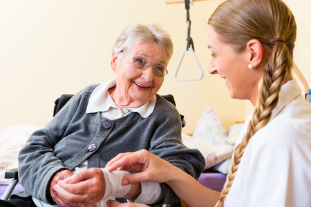 Nurse taking care of senior woman in retirement home bandaging a wound Stockfoto
