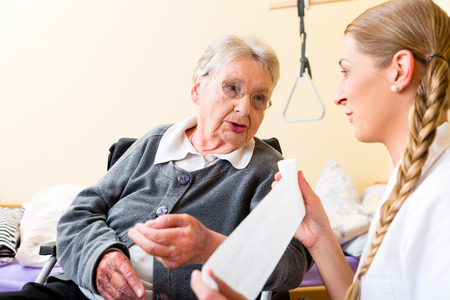 happy patient: Nurse taking care of senior woman in retirement home bandaging a wound Stock Photo