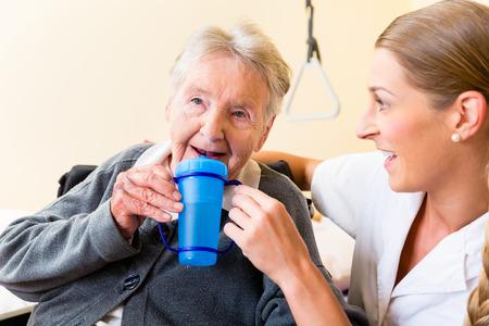 an elderly person: Enfermera en enfermer�a dar casa de beber a la mujer mayor que se sienta en la silla de ruedas Foto de archivo