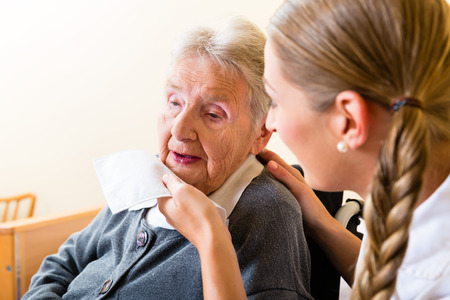 Nurse wiping mouth of elderly senior woman in nursing home Stock Photo