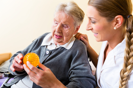 sillas de ruedas: Enfermera que da la terapia f�sica con el bal�n de masaje a la mujer mayor en silla de ruedas Foto de archivo