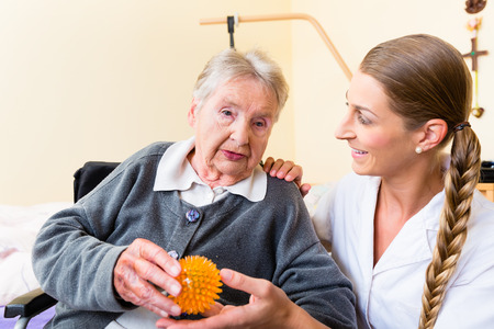 Nurse giving physical therapy with massage ball to senior woman in wheelchair photo