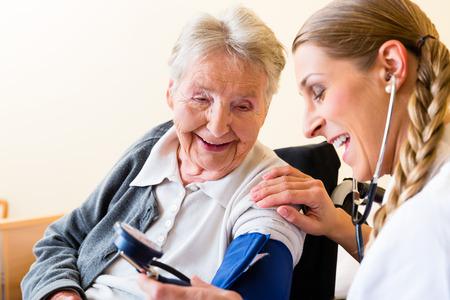 enfermera: Amamantar a medir la presión arterial en el paciente mujer senior en casa de retiro