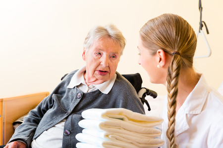 bejaardenhuis: Nurse bringing supplies to senior woman in retirement home Stockfoto