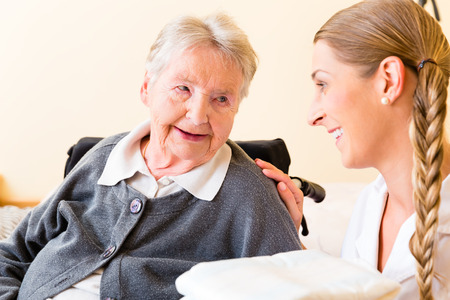 social care: Nurse bringing supplies to senior woman in retirement home Stock Photo