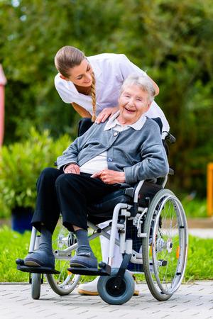 Nurse pushing senior woman in wheelchair on walk thru garden in summer