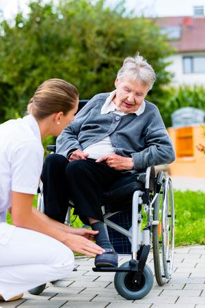 geriatric: Nurse pushing senior woman in wheelchair on walk thru garden in summer