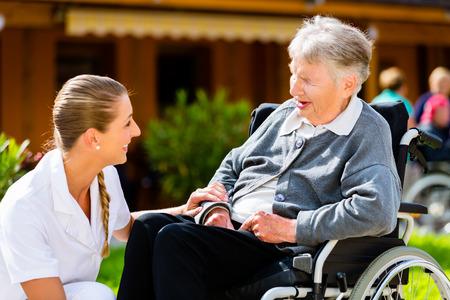 silla de rueda: Enfermera empujando la mujer mayor en silla de ruedas a paseo a trav�s del jard�n en verano