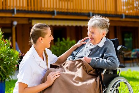 2 people at home: Nurse pushing senior woman in wheelchair on walk thru garden in summer