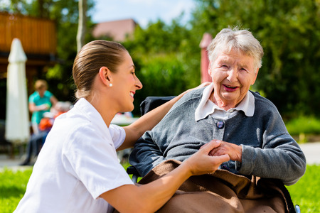 empathy: Nurse holding hands with senior woman sitting in wheelchair in garden of retirement home