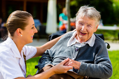empatia: Enfermera de la mano con una mujer mayor que se sienta en la silla de ruedas en el jard�n de la casa de retiro Foto de archivo