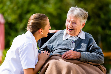 home care: Nurse holding hands with senior woman sitting in wheelchair in garden of retirement home