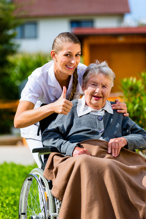 wheelchair: Senior woman in nursing home with nurse in garden sitting in wheelchair giving the thumbs up sign