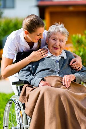 adulto mayor feliz: Mujer mayor en un hogar de ancianos con la enfermera en el jard�n sentado en silla de ruedas