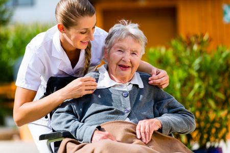 discapacidad: Mujer mayor en un hogar de ancianos con la enfermera en el jard�n sentado en silla de ruedas