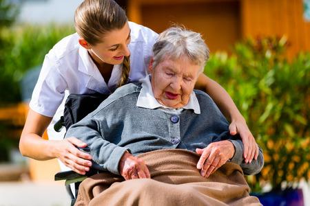 geriatric care: Senior woman in nursing home with nurse in garden sitting in wheelchair