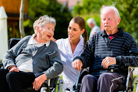 Old couple, senior man and woman, in garden of retirement home with nurse