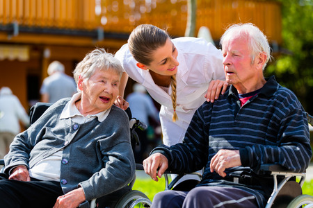 Old couple, senior man and woman, in garden of retirement home with nurse photo