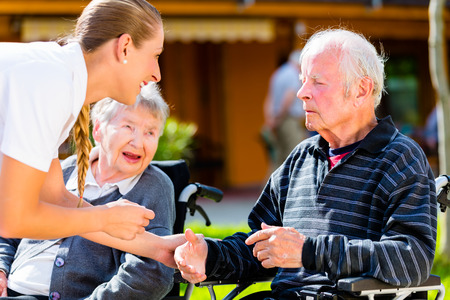 wheelchair woman: Seniors, couple of man and woman sitting in wheelchair, nurse holding hands with them Stock Photo