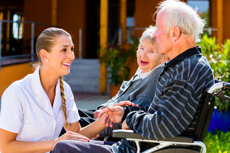 Seniors, couple of man and woman sitting in wheelchair, nurse holding hands with them photo