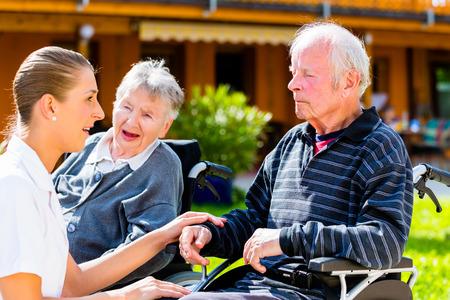 gente sentada: Personas Mayores, pareja de hombre y mujer sentada en silla de ruedas, la enfermera de la mano con ellos