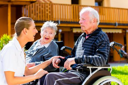 personas sentadas: Personas Mayores, pareja de hombre y mujer sentada en silla de ruedas, la enfermera de la mano con ellos
