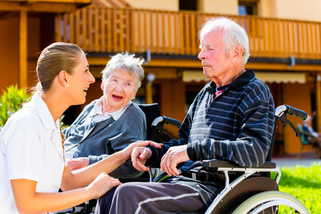 home care nurse: Seniors, couple of man and woman sitting in wheelchair, nurse holding hands with them Stock Photo