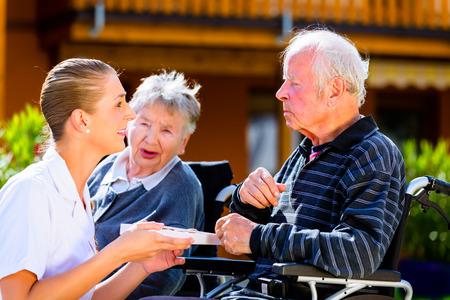 Senioren, Paar von Mann und Frau sitzt im Rollstuhl, essen Süßigkeiten im Garten des Pflegeheim