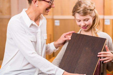 home improvement store: Family choosing parquet wood floor in home improvement store