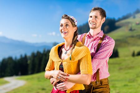 tracht: Couple in Tracht on Alp mountain summit at vacation
