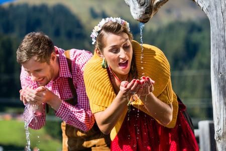 source d eau: Couple dans les montagnes d'alpage de l'eau potable de la source, scène réglée avec les vêtements traditionnels