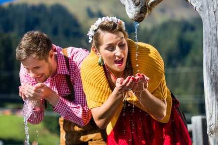water source: Couple in alp mountains drinking water from source, scene set with traditional clothing Stock Photo